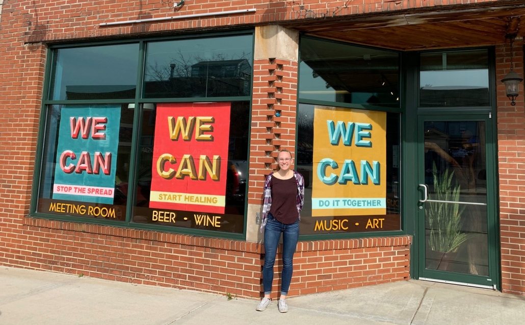 "Artist Maddie Bebrun stands outside the Firefly Coffeehouse where her original ""WE CAN"" posters are on display"